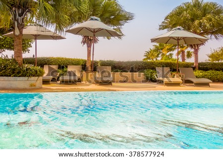 Umbrella and chair around beautiful luxury swimming pool in hotel resort - Vintage and boost up color Processing