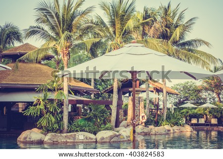 Umbrella and chair around luxury swimming pool landscape with palm tree in hotel resort - Vintage Filter and Boost up color Processing