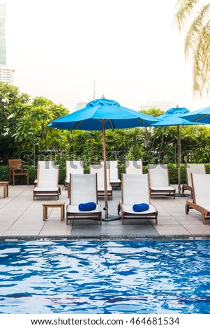 Umbrella and chair decoration around swimming pool  in hotel and resort - Sunflare effect