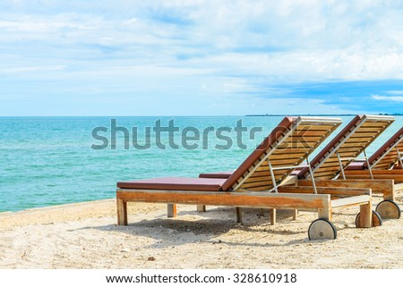Umbrella and chair on beautiful tropical beach - summer vacation background