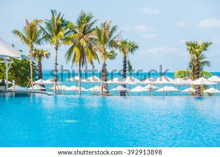 Umbrella and empty chair around swimming pool in hotel resort - Boost up color Processing