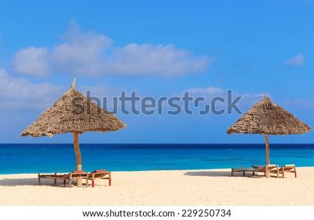 Umbrella and lounges at the shore of Indian Ocean, Kendwa beach, Zanzibar, Tanzania - stock photo