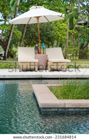 Umbrella and recliners alongside a pool at a tropical island resort with a wooden hut and trees behind - stock photo