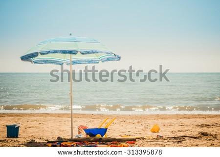 Umbrella beach and children beach toys on beach in summer day. - stock photo