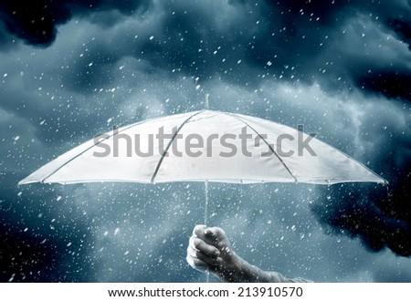 Umbrella in hand under raindrops of thunderstorm - stock photo