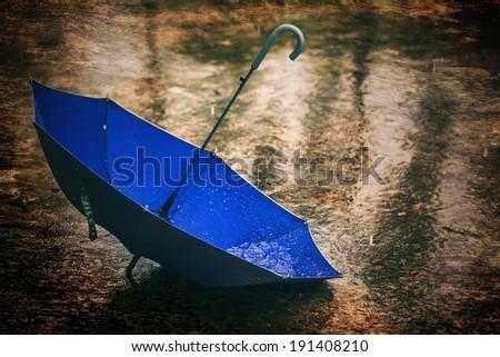 Umbrella in the rain antique style - stock photo
