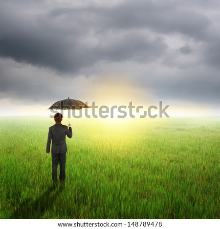 Umbrella man standing to raincloud in grassland with umbrella
