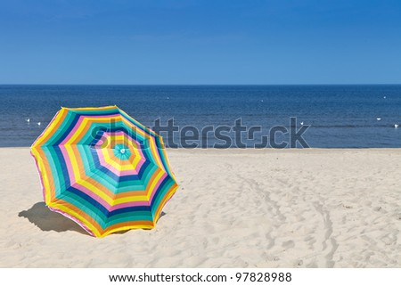 Umbrella on a sandy beach, summertime - stock photo