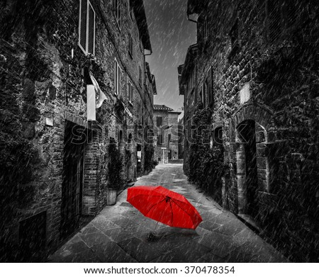 Umbrella on dark narrow street in an old Italian town in Tuscany, Italy. Raining. Black and white with red - stock photo