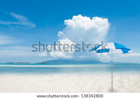 Umbrella on white sand beach and blue sky sea background