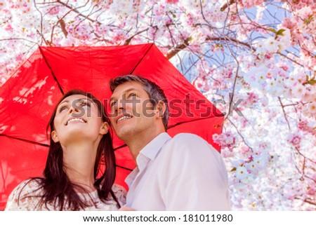 umbrella safety younger couple smiling - stock photo