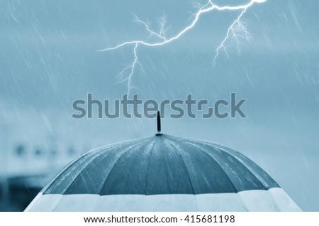 umbrella under the rain with lightning at horizon - stock photo