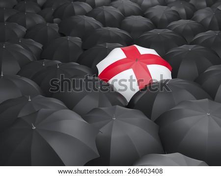 Umbrella with flag of england over black umbrellas - stock photo