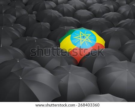 Umbrella with flag of ethiopia over black umbrellas - stock photo