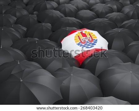 Umbrella with flag of french polynesia over black umbrellas - stock photo