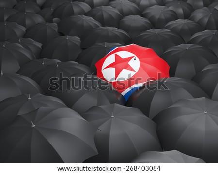 Umbrella with flag of korea north over black umbrellas - stock photo