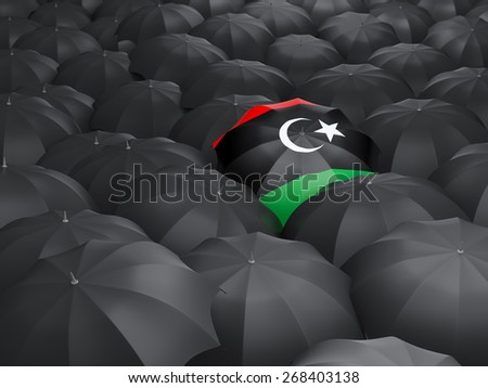 Umbrella with flag of libya over black umbrellas - stock photo