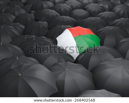 Umbrella with flag of madagascar over black umbrellas - stock photo