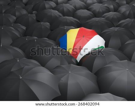 Umbrella with flag of seychelles over black umbrellas - stock photo