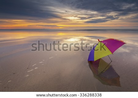 Umbrella with reflection at the beach during sunset. Sabah Borneo Malaysia  - stock photo