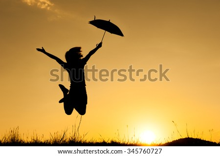 Umbrella woman jumping and sunset silhouette with copy space.