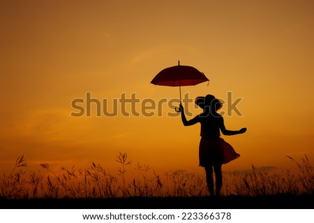 Umbrella woman stand and sunset silhouette