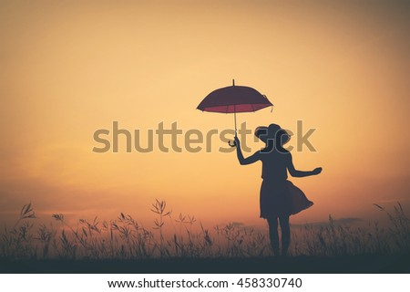Umbrella woman stand and sunset silhouette.Vintage tone.