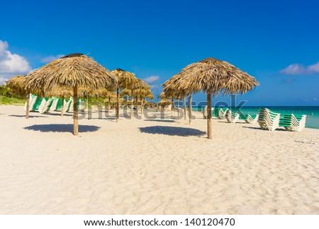 Umbrellas and beach beds on the beach of Varadero in Cuba - stock photo
