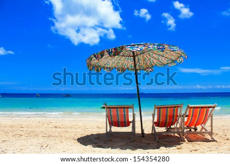 Umbrellas and beach chairs on Koh Larn Thailand. - stock photo
