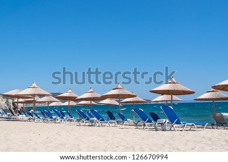 Umbrellas and chairs on the sandy beach with sea and clear sky in the background - copy space on the sky - stock photo