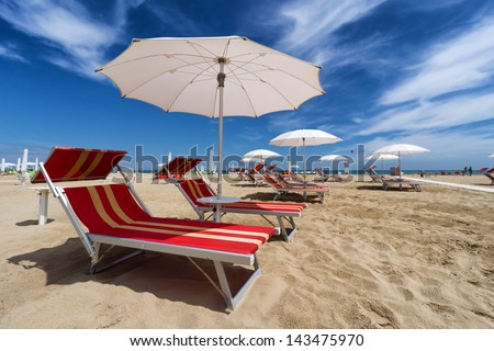 Umbrellas and sunbeds in Rimini and Riccione Beach, Italy - stock photo