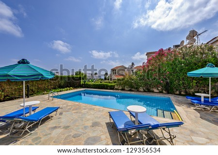 Umbrellas and sunbeds near the pool in the yard - stock photo