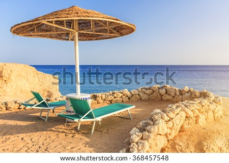 Umbrellas and two empty deckchairs on the shore sand beach - stock photo