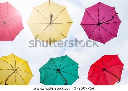 umbrellas in the sky rainbow the diversity of colors - stock photo