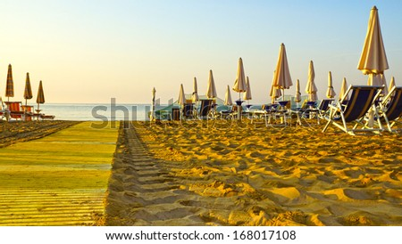 umbrellas on the beaches of Italy in the morning hour - stock photo