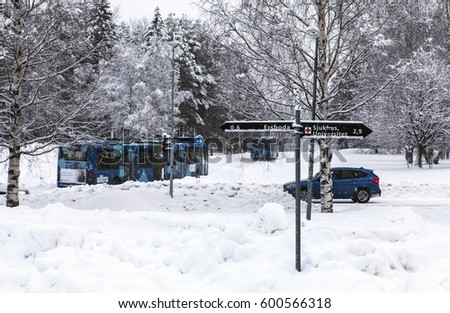 UMEA, SWEDEN ON MARCH 02. View of a sign, buses and a vehicle along a snowy road on March 02, 2017 in Umea, Sweden. Trees in the background.