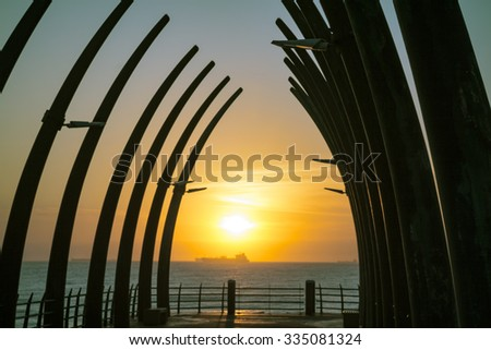 Umhlanga Pier in Durban South Africa in the morning Sunrise over the Indian Ocean with ships on the horizon - stock photo