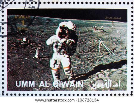 UMM AL-QUWAIN - CIRCA 1972: a stamp printed in the Umm al-Quwain shows Astronaut walks on the Surface of the Moon, Moon-landing, Apollo, circa 1972 - stock photo