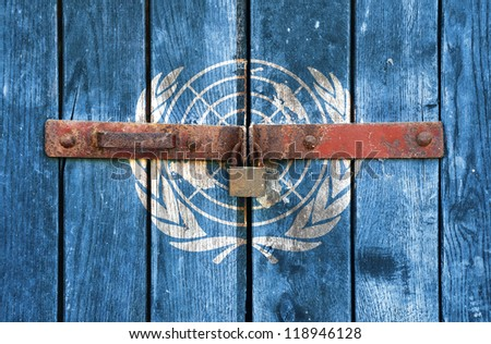 UN flag on the background of old locked doors - stock photo