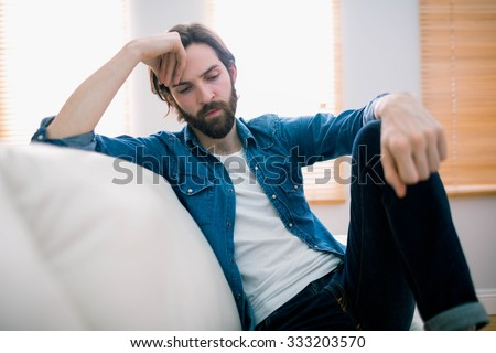 Unahppy man thinking on his sofa at home in the living room - stock photo
