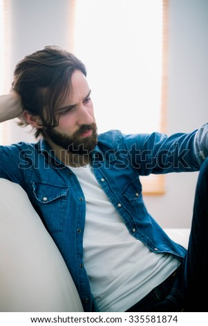 Unahppy man thinking on his sofa at home in the living room