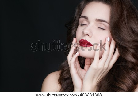 Unassuming beauty. Portrait of an attractive young brunette female touching her face sensually with her eyes closed on black background.  - stock photo