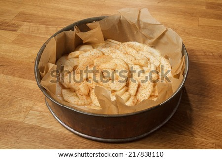 Unbaked apple pie in a metal spring form standing on a wooden table - stock photo