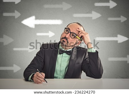 Uncertain guy looking at arrows. Man full of doubts hesitation. Closeup portrait puzzled business man thinking deciding something confused unsure isolated grey wall background. Emotion face expression - stock photo
