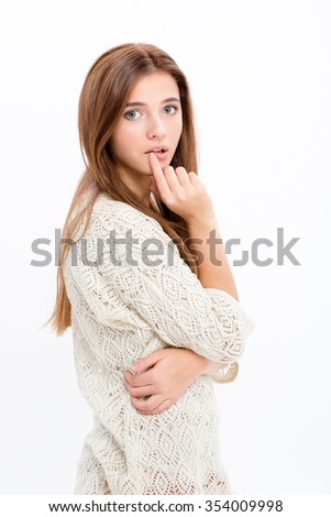 Unconfident pensive pretty young woman looking back over white background - stock photo