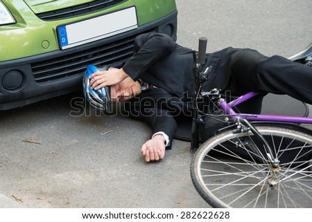 Unconscious Male Cyclist Lying On Road After Road Accident - stock photo