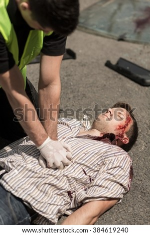 Unconscious man lying on the street is being resuscitated