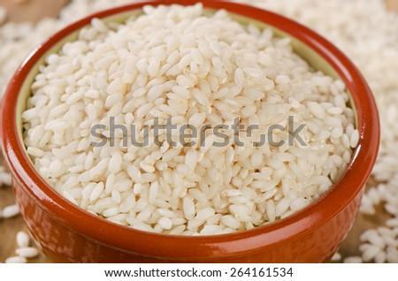 Uncooked arborio rice in bowl. Selective focus - stock photo