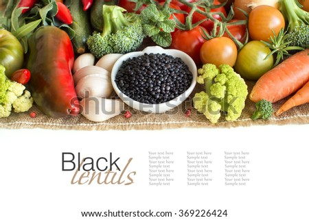 Uncooked black lentils in a bowl with vegetables isolated on white - stock photo
