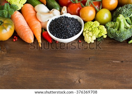 Uncooked black lentils in a bowl with vegetables on a wooden table - stock photo